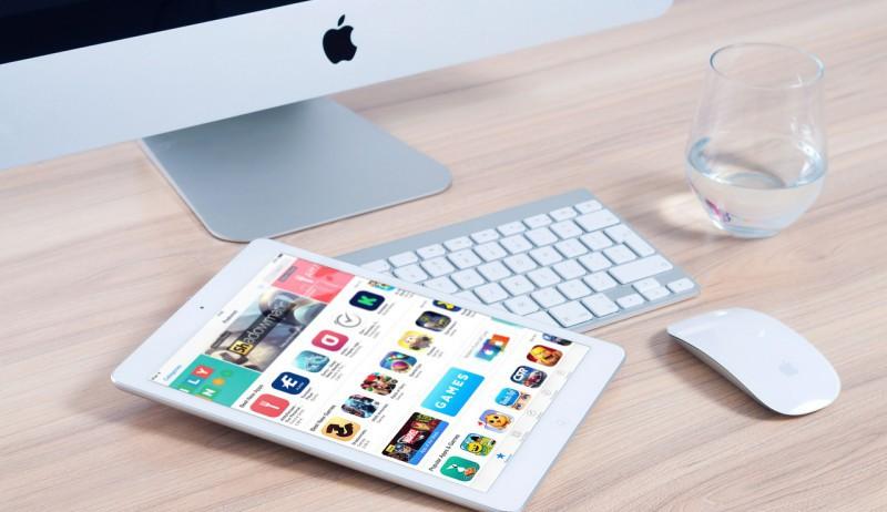 En Mac og en iPad på en pult.
