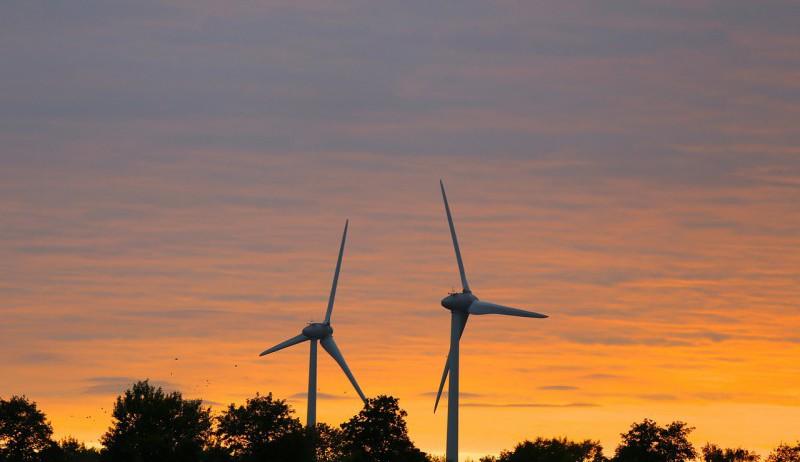 To vindmøller i solnedgang.
