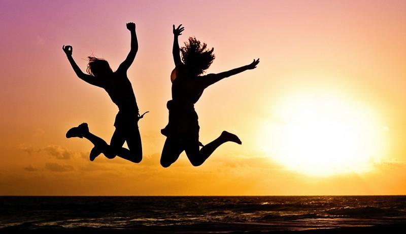 To jenter som hopper med solnedgangen bak seg.