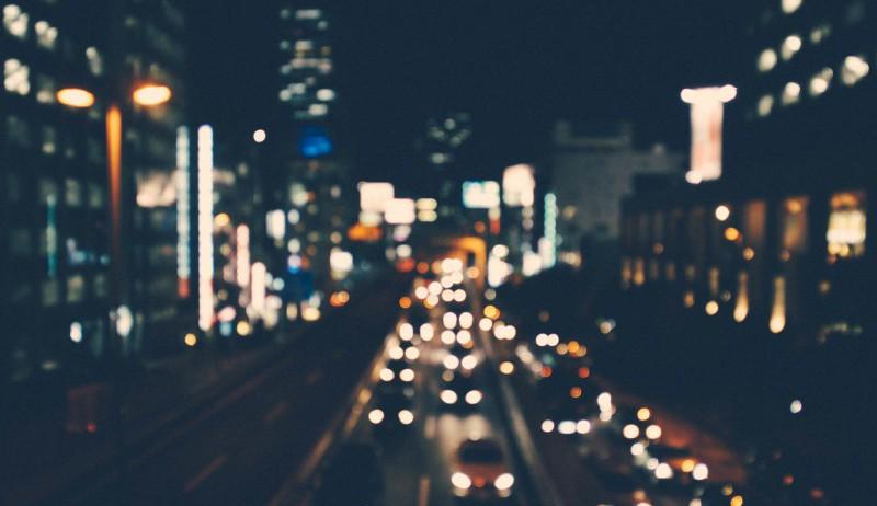 En mørk bygate opplyst av biler og andre lys.